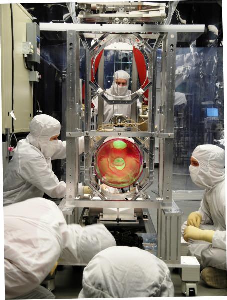 Equipo del laboratorio LIGO ajustando la suspensión de un sistema óptico